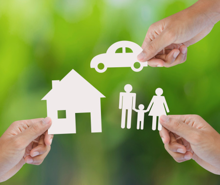 Hand holding a paper home, car, family on green background